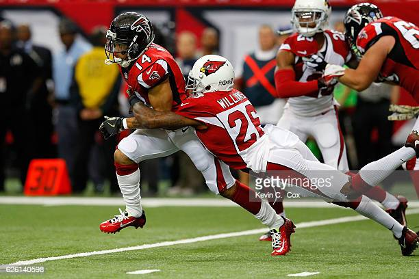 Eric Weems of the Atlanta Falcons returns a kick off against Brandon Williams of the Arizona Cardinals during the first half at the Georgia Dome on...