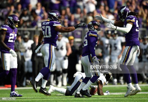 Eric Wilson and Emmanuel Lamur of the Minnesota Vikings celebrate a tackle by teammate Marcus Sherels at the end of the first half of the game...