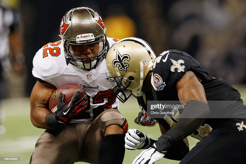 Eric Wright of the Tampa Bay Buccaneers is tackled by Roman Harper of the New Orleans Saints at the MercedesBenz Superdome on December 16 2012 in New...