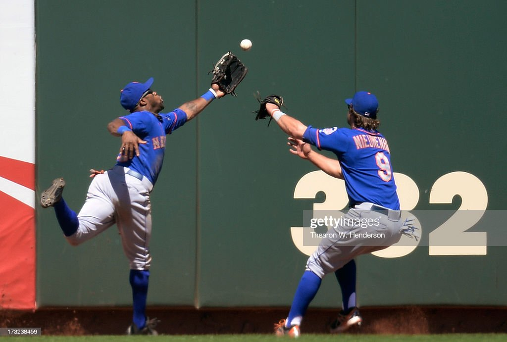 Eric Young #22 and Kirk Nieuwenhuis #9 of the New York Mets avoid colliding with each other as they are unable to make the catch of this ball that goes for a triple off the bat of Brandon Belt #9 of the San Francisco Giants in the ninth inning at AT&T Park on July 10, 2013 in San Francisco, California. Belt later scored but the Mets won the game 7-2.