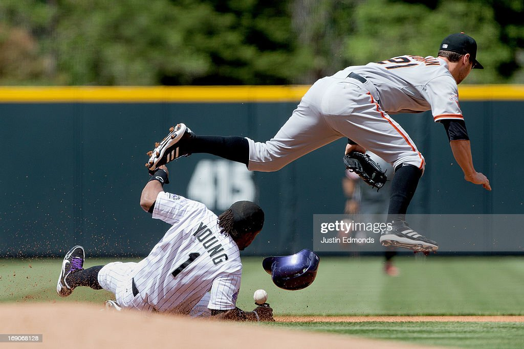 Eric Young Jr. #1 of the Colorado Rockies slides in safely for a stolen base and takes out second baseman Nick Noonan #21 of the San Francisco Giants during the first inning at Coors Field on May 19, 2013 in Denver, Colorado.