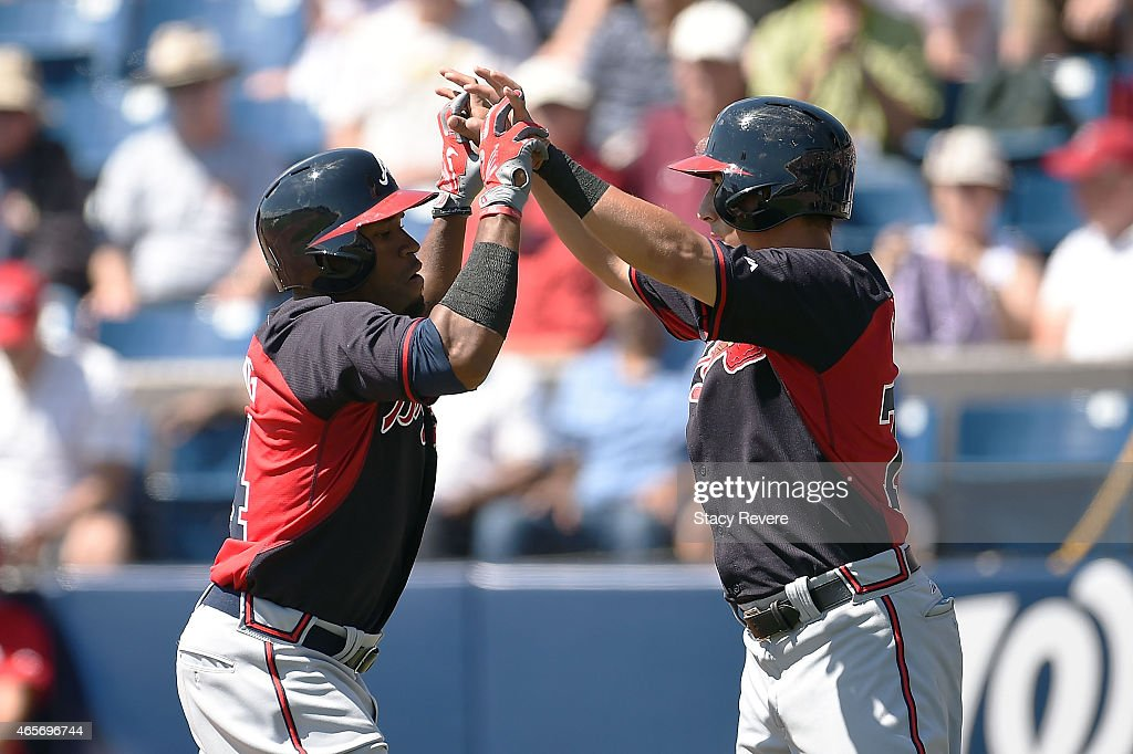 Eric Young Jr. #4 of the Atlanta Braves is congratulated by Daniel Castro #77 following a home run during the third inning of a spring training game against the Washington Nationals at Space Coast Stadium on March 9, 2015 in Viera, Florida.