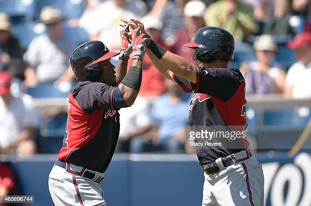 Eric Young Jr #4 of the Atlanta Braves is congratulated by Daniel Castro following a home run during the third inning of a spring training game...