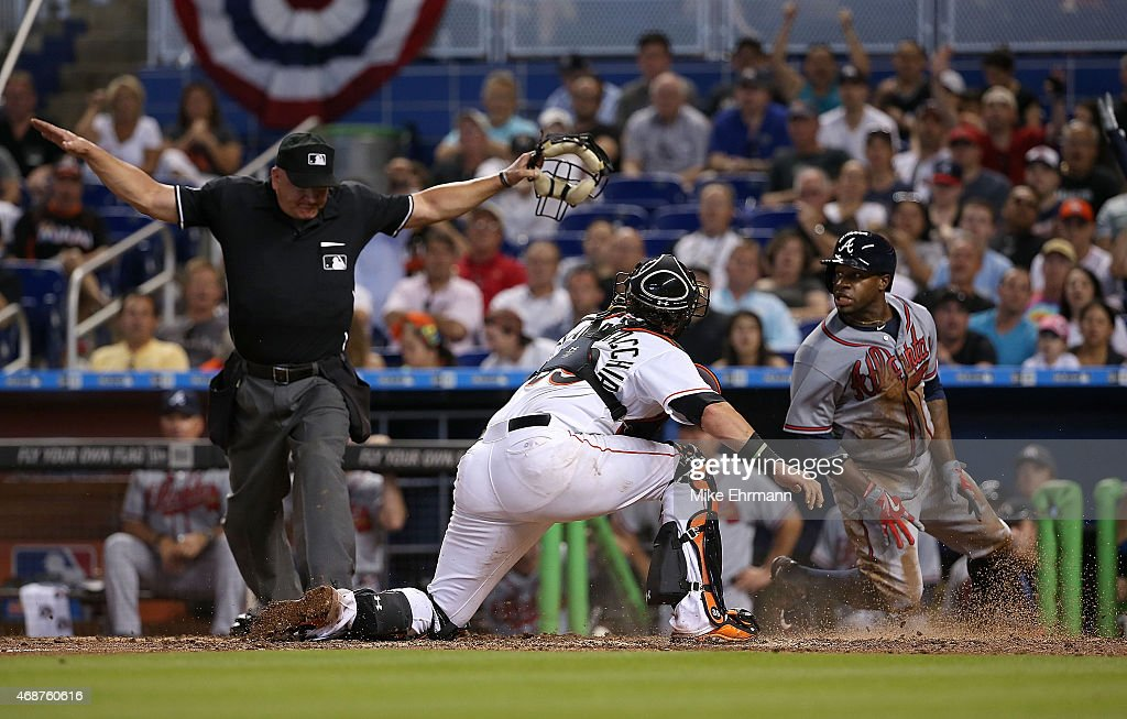 Eric Young Jr #4 of the Atlanta Braves slides past Jarrod Saltalamacchia of the Miami Marlins to score the go ahead run during Opening Day at Marlins...