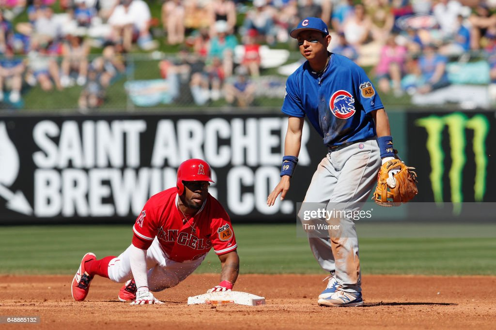 Eric Young Jr. #8 of the Los Angeles Angels dives back to second base as Munenori Kawasaki #66 of the Chicago Cubs awaits a throw in the second inning during the spring training game at Tempe Diablo Stadium on March 6, 2017 in Tempe, Arizona.