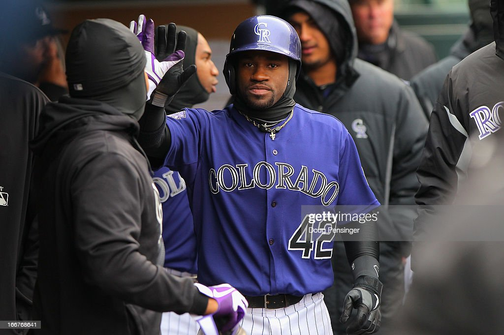 Eric Young Jr. of the Colorado Rockies celebrates in the dugout after scoring against the New York Mets in the fifth inning at Coors Field on April 16, 2013 in Denver, Colorado. All uniformed team members are wearing jersey number 42 in honor of Jackie Robinson Day.