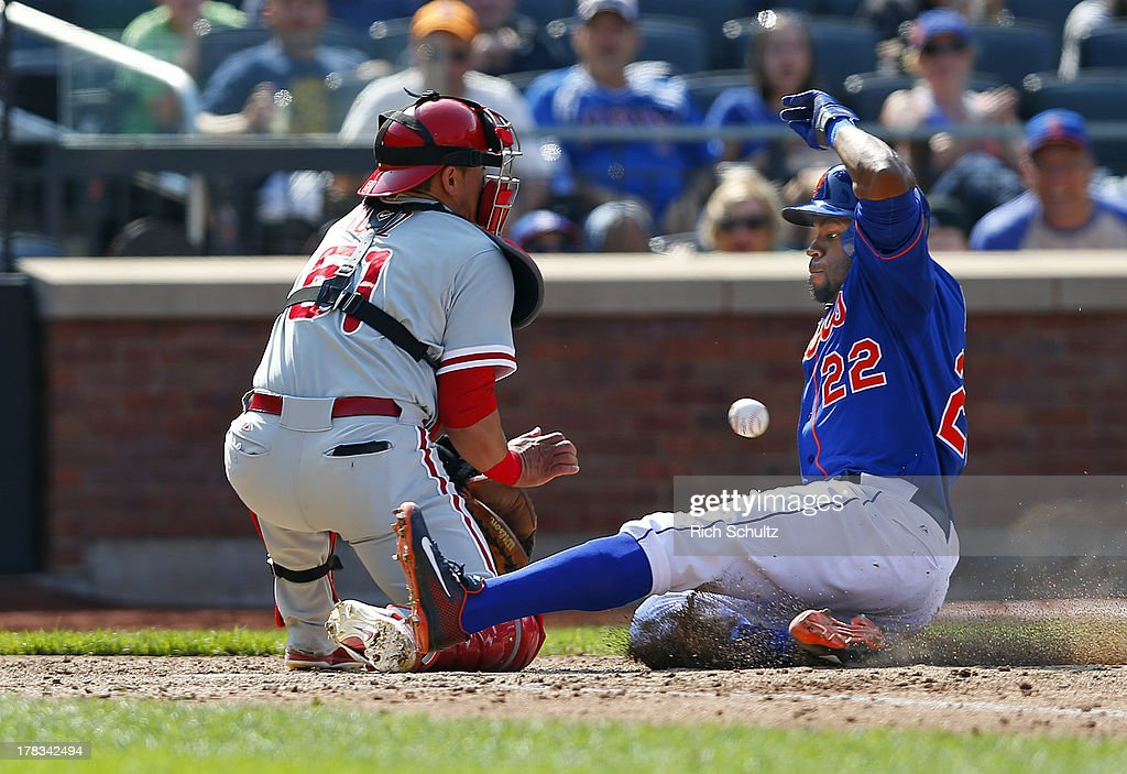 Eric Young #22 of the New York Mets scores on a single by Daniel Murphy #28 before catcher Carlos Ruiz #51 of the Philadelphia Phillies gets the ball in the sixth inning on August 29, 2013 at Citi Field in the Flushing neighborhood of the Queens borough of New York City.