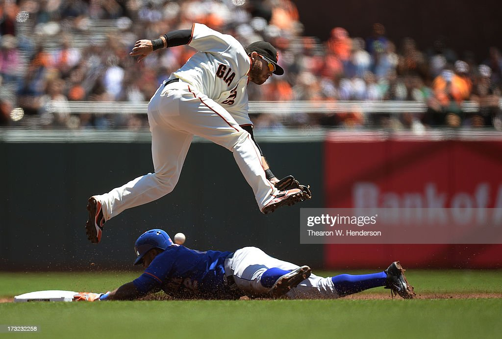 Eric Young #22 of the New York Mets steals second base as the throw goes into centerfield past <a gi-track='captionPersonalityLinkClicked' href=/galleries/search?phrase=Brandon+Crawford&family=editorial&specificpeople=5580312 ng-click='$event.stopPropagation()'>Brandon Crawford</a> #35 of the San Francisco Giants in the first inning at AT&T Park on July 10, 2013 in San Francisco, California. Young went to third base on the throwing error by catcher Buster Posey #28.