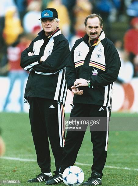 Erich Ribbeck Teamchef der deutschen FußballNationalmannschaft und Nationaltrainer Uli Stielike beobachten den Spielverlauf Ribbeck trägt eine...