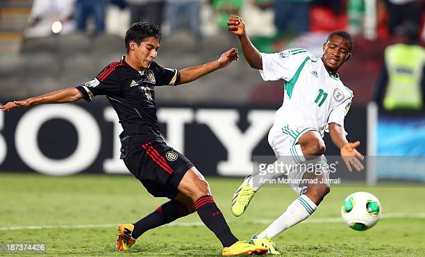 Erick Aguirre of Mexico scores an own goal under pressure from Musa Yahaya of Nigeria during the FIFA U17 World cup UAE 2013 Final match between...
