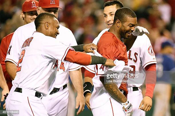 Erick Aybar congratulates teammate Howie Kendrick of the Los Angeles Angels of Anaheim after driving in the winning run to defeat the Texas Rangers...