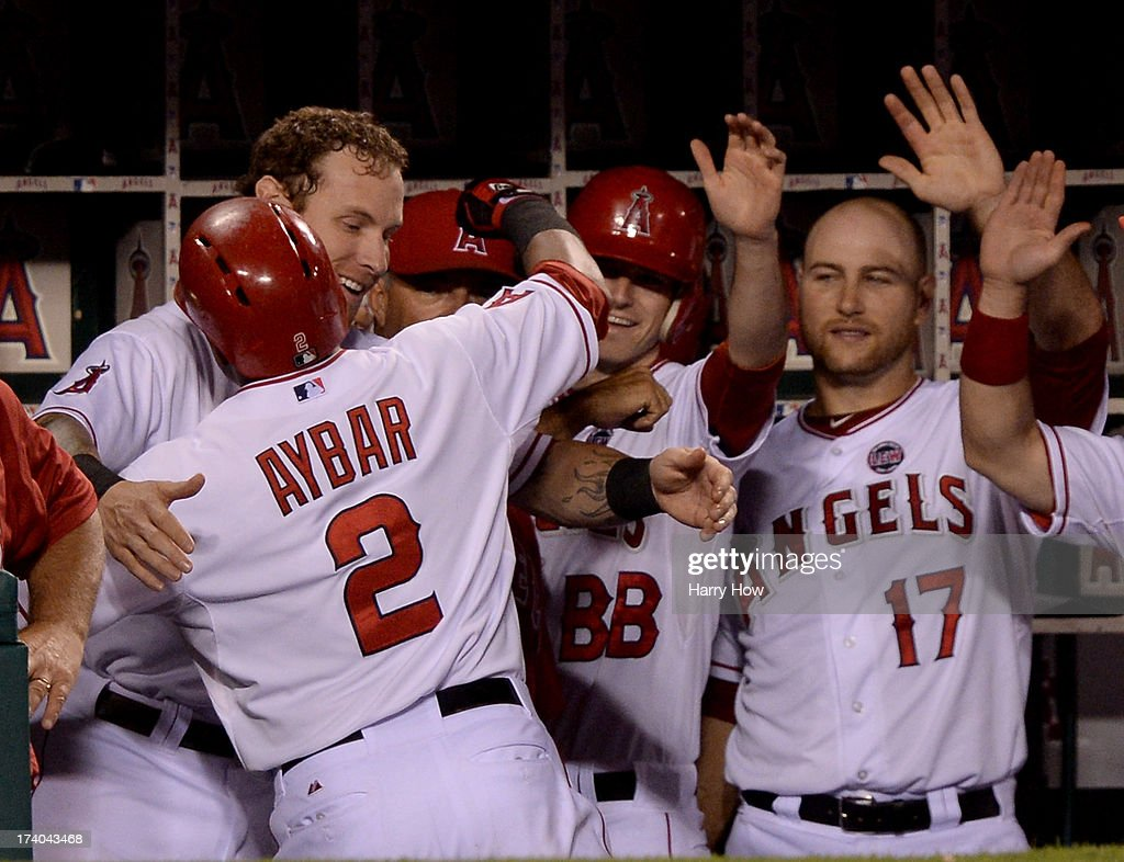 Erick Aybar #2 of the Los Angeles Angels celebrates his solo homerun with Josh Hamilton #32 and Chris Iannetta #17 for a 3-0 lead over the Oakland Athletics during the fifth inning at Angel Stadium of Anaheim on July 19, 2013 in Anaheim, California.