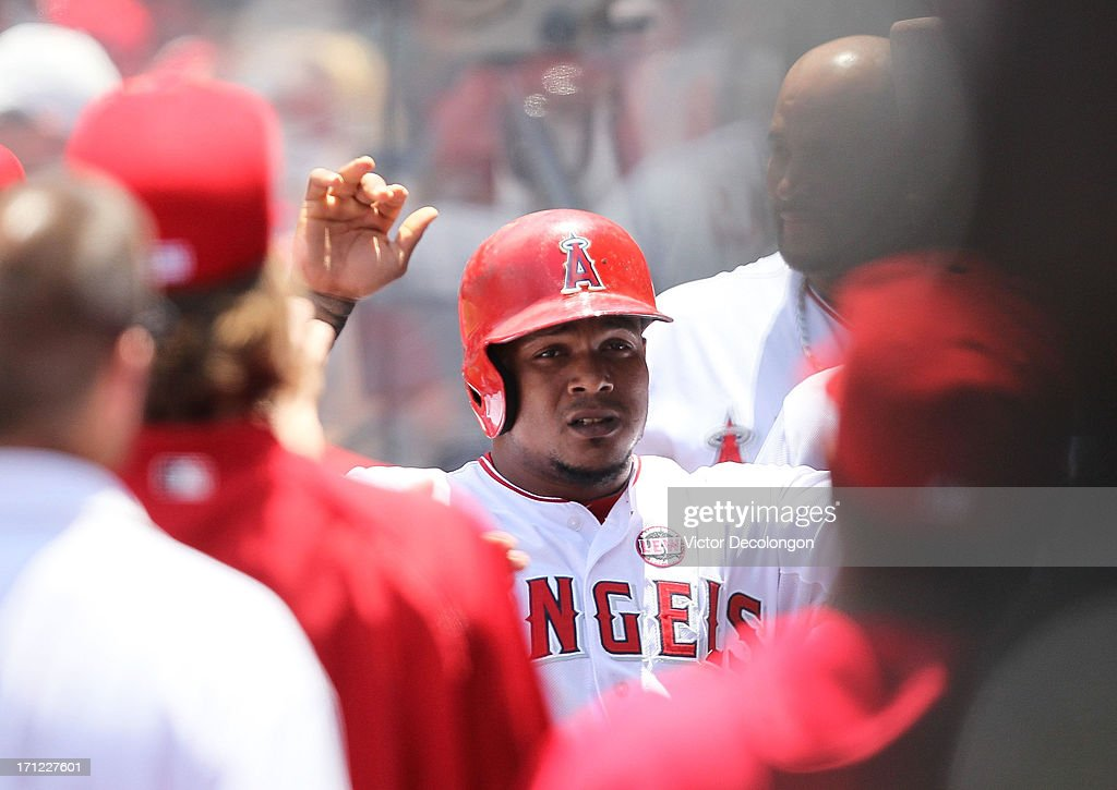 Erick Aybar #2 of the Los Angeles Angels of Anaheim celebrates with teammates in the dugout after scoring on a single to left by J.B. Shuck #39 (not in photo) during the MLB game against the Pittsburgh Pirates at Angel Stadium of Anaheim on June 23, 2013 in Anaheim, California.