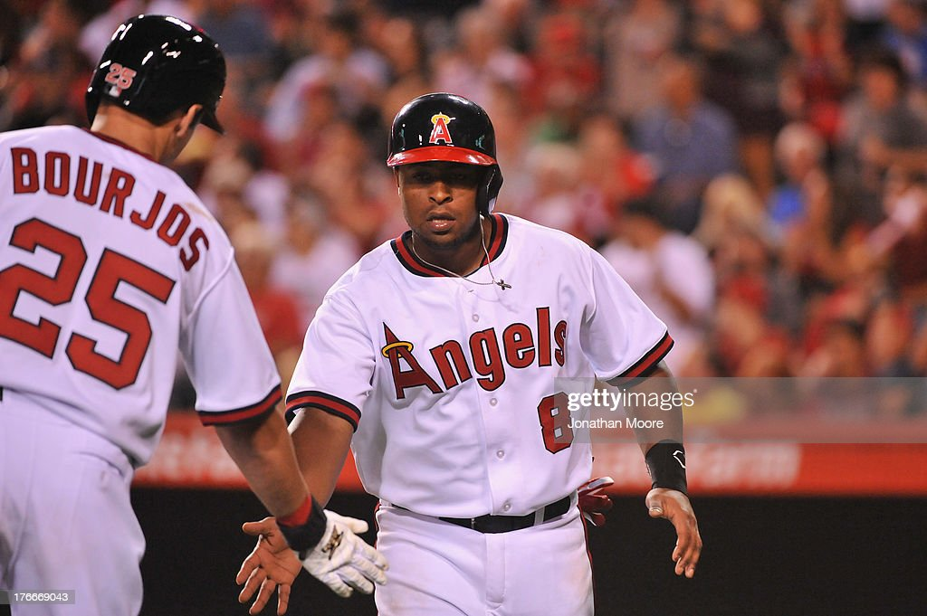 <a gi-track='captionPersonalityLinkClicked' href=/galleries/search?phrase=Erick+Aybar&family=editorial&specificpeople=551376 ng-click='$event.stopPropagation()'>Erick Aybar</a> #2 of the Los Angeles Angels of Anaheim celebrates with Peter Bourjos #25 after scoring on a ground ball hit by Hank Conger #16 (not pictured) in the fifth inning during a game against the Houston Astros at Angel Stadium of Anaheim on August 16, 2013 in Anaheim, California.