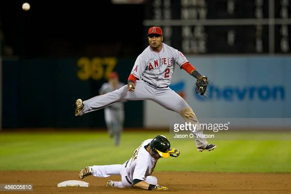 Erick Aybar of the Los Angeles Angels of Anaheim completes a double play over Josh Reddick of the Oakland Athletics during the seventh inning at Oco...