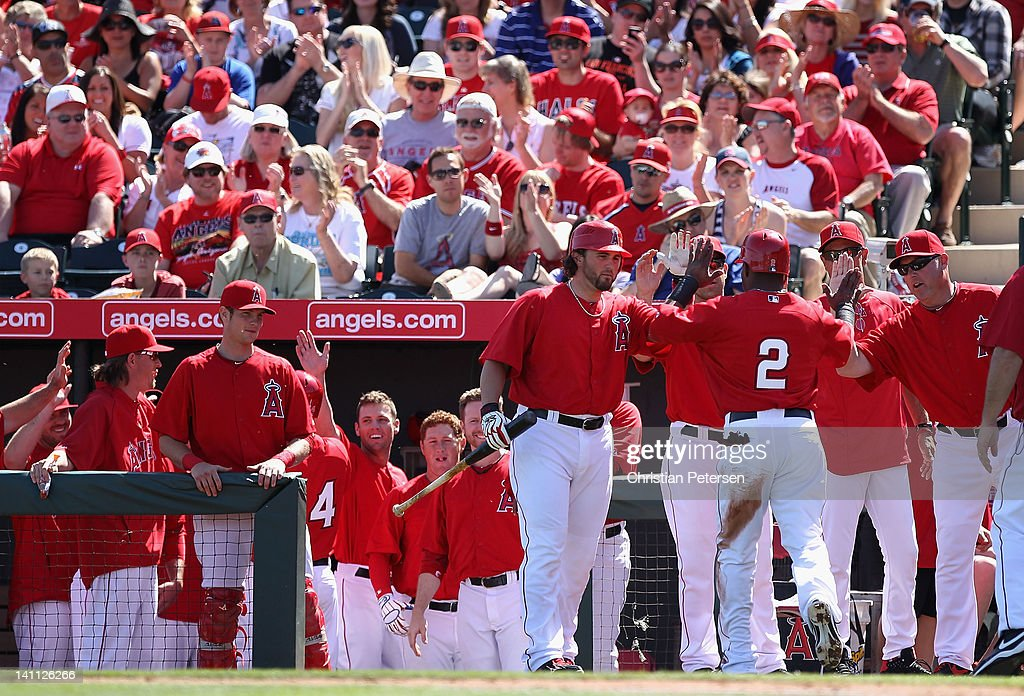 <a gi-track='captionPersonalityLinkClicked' href=/galleries/search?phrase=Erick+Aybar&family=editorial&specificpeople=551376 ng-click='$event.stopPropagation()'>Erick Aybar</a> #2 of the Los Angeles Angels of Anaheim high-fives Bobby Wilson #46 after scoring a run against the San Francisco Giants during the first inning of the spring training game at Tempe Diablo Stadium on March 10, 2012 in Tempe, Arizona.