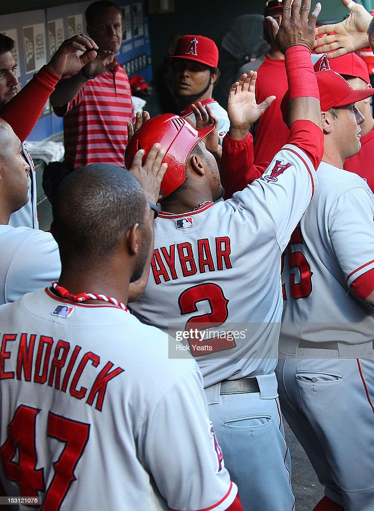 <a gi-track='captionPersonalityLinkClicked' href=/galleries/search?phrase=Erick+Aybar&family=editorial&specificpeople=551376 ng-click='$event.stopPropagation()'>Erick Aybar</a> #2 of the Los Angeles Angels of Anaheim is congratulated by his team mates for scoring in the first inning in game two of the double header against the Texas Rangers at Rangers Ballpark in Arlington on September 30, 2012 in Arlington, Texas.