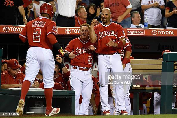 Erick Aybar of the Los Angeles Angels of Anaheim returns to the dugout to celebrate with teammates Kole Calhoun and Albert Pujols after hitting a...