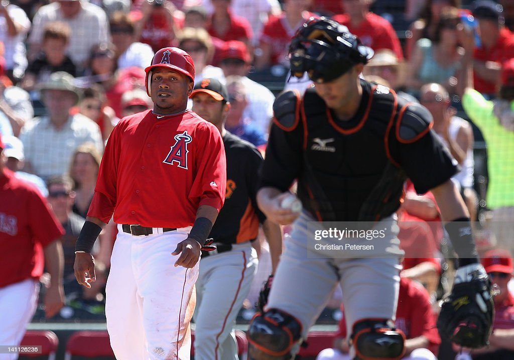 <a gi-track='captionPersonalityLinkClicked' href=/galleries/search?phrase=Erick+Aybar&family=editorial&specificpeople=551376 ng-click='$event.stopPropagation()'>Erick Aybar</a> #2 of the Los Angeles Angels of Anaheim scores a first inning run past catcher <a gi-track='captionPersonalityLinkClicked' href=/galleries/search?phrase=Eli+Whiteside&family=editorial&specificpeople=836374 ng-click='$event.stopPropagation()'>Eli Whiteside</a> #22 of the San Francisco Giants during the spring training game at Tempe Diablo Stadium on March 10, 2012 in Tempe, Arizona.
