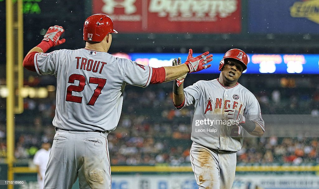 <a gi-track='captionPersonalityLinkClicked' href=/galleries/search?phrase=Erick+Aybar&family=editorial&specificpeople=551376 ng-click='$event.stopPropagation()'>Erick Aybar</a> #2 of the Los Angeles Angels of Anaheim scores on the sacrifice fly by J. B. Shuck #39 and is contradulated by teammate <a gi-track='captionPersonalityLinkClicked' href=/galleries/search?phrase=Mike+Trout&family=editorial&specificpeople=7091306 ng-click='$event.stopPropagation()'>Mike Trout</a> #27 during the seventh inning of the game against the Detroit Tigers at Comerica Park on June 25, 2013 in Detroit, Michigan. The Angels defeated the 14-8.