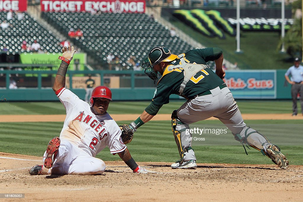 <a gi-track='captionPersonalityLinkClicked' href=/galleries/search?phrase=Erick+Aybar&family=editorial&specificpeople=551376 ng-click='$event.stopPropagation()'>Erick Aybar</a> #2 of the Los Angeles Angels of Anaheim slides safely past the tag of catcher Stephen Vogt #21 of the Oakland Athletics and scores a run in the fourth inning at Angel Stadium of Anaheim on September 25, 2013 in Anaheim, California.
