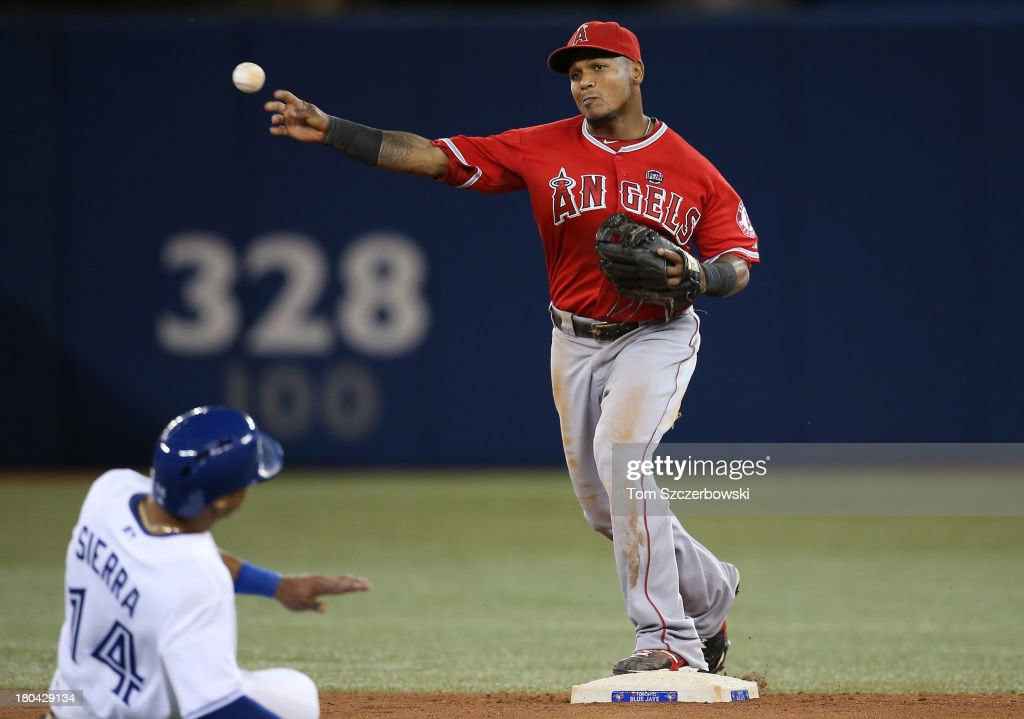 <a gi-track='captionPersonalityLinkClicked' href=/galleries/search?phrase=Erick+Aybar&family=editorial&specificpeople=551376 ng-click='$event.stopPropagation()'>Erick Aybar</a> #2 of the Los Angeles Angels of Anaheim turns a double play in the fifth inning during MLB game action as <a gi-track='captionPersonalityLinkClicked' href=/galleries/search?phrase=Moises+Sierra&family=editorial&specificpeople=7509137 ng-click='$event.stopPropagation()'>Moises Sierra</a> #14 of the Toronto Blue Jays slides on September 12, 2013 at Rogers Centre in Toronto, Ontario, Canada.