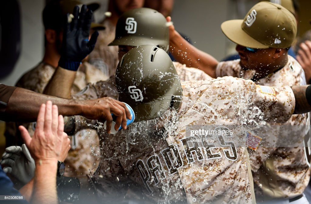 Erick Aybar #8 of the San Diego Padres is congratulated after hitting a two-run home run during the fourth inning of a baseball game against the Los Angeles Dodgers at PETCO Park on September 3, 2017 in San Diego, California.