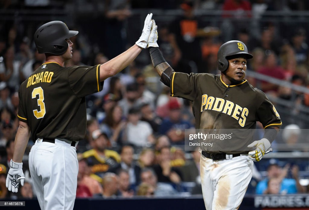 Erick Aybar #8 of the San Diego Padres, right, is congratulated by Clayton Richard #3 after scoring during the fourth inning of a baseball game against the San Francisco Giants at PETCO Park on July 14, 2017 in San Diego, California.