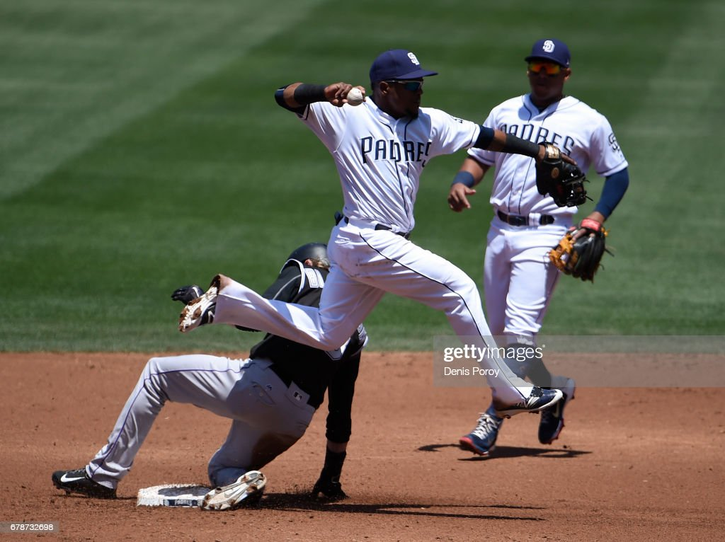 Erick Aybar #8 of the San Diego Padres throws over Charlie Blackmon #19 of the Colorado Rockies as he tries to turn a double play during the third inning of a baseball game at PETCO Park on May 4, 2017 in San Diego, California.