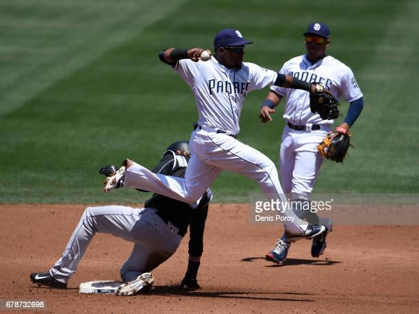 Erick Aybar of the San Diego Padres throws over Charlie Blackmon of the Colorado Rockies as he tries to turn a double play during the third inning of...