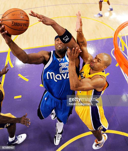 Erick Dampier of the Dallas Mavericks fight for a rebound against Derek Fisher of the Los Angekes Lakers during the basketball game at Staples Center...