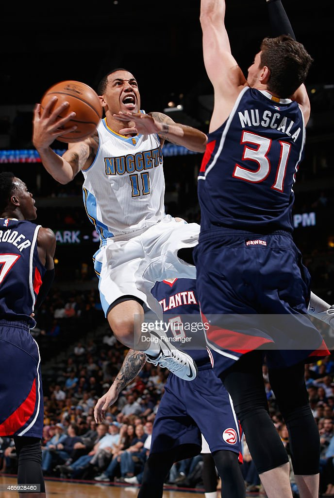 <a gi-track='captionPersonalityLinkClicked' href=/galleries/search?phrase=Erick+Green&family=editorial&specificpeople=7348606 ng-click='$event.stopPropagation()'>Erick Green</a> #11 of the Denver Nuggets lays up a shot against <a gi-track='captionPersonalityLinkClicked' href=/galleries/search?phrase=Mike+Muscala&family=editorial&specificpeople=7563430 ng-click='$event.stopPropagation()'>Mike Muscala</a> #31 of the Atlanta Hawks at Pepsi Center on March 11, 2015 in Denver, Colorado. The Nuggets defeated the Hawks 115-102.
