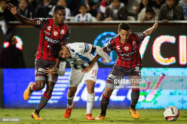 Erick Gutierrez of Pachuca struggles for the ball with Brayan Beckeles and Igor Lichnovsky of Necaxa during the 12th round match between Pachuca and...