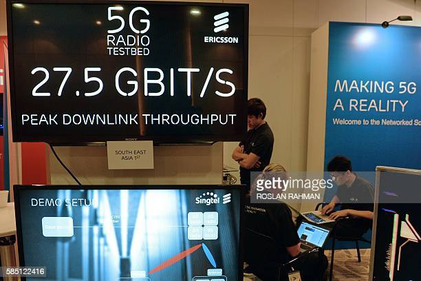Ericsson engineers work on a 5G radio testbed booth during a demonstration at SingTel in Singapore on August 2 2016 SingTel and Ericsson the Swedish...
