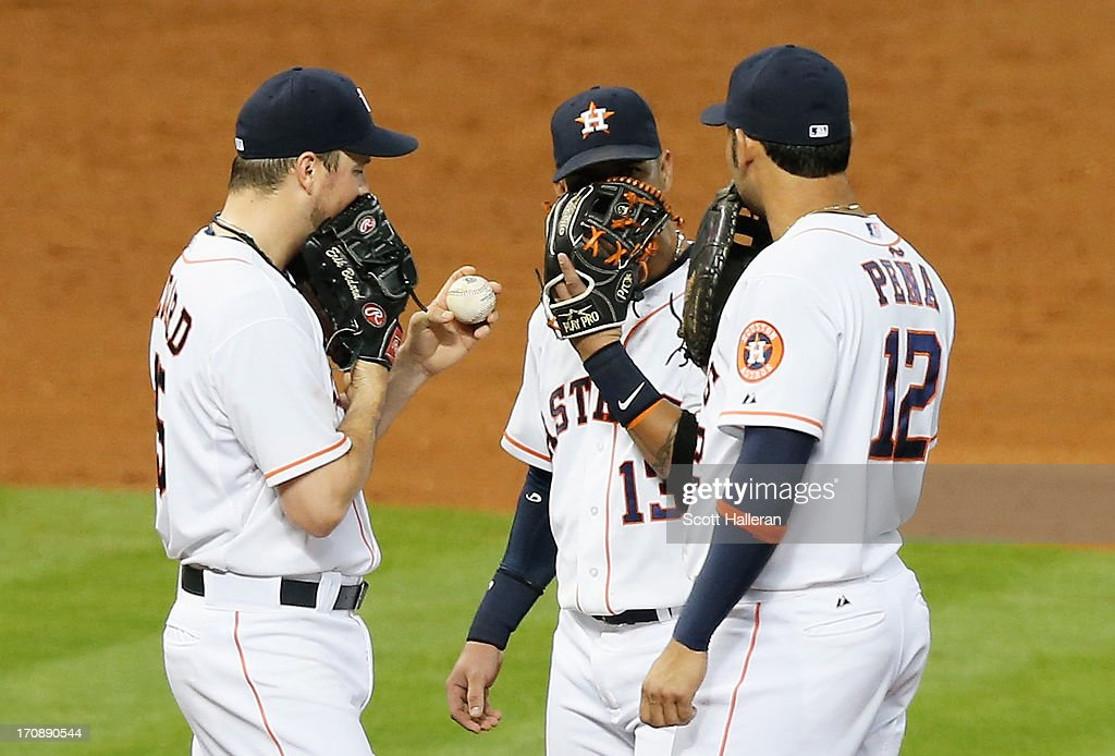 Erik Bedard of the Houston Astros chats with teammates Ronny Cedeno and Carlos Pena in the sixth inning during the game against the Milwaukee Brewers...