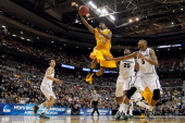 Erik Buggs of the Valparaiso Crusaders drives for a shot attempt against Adreian Payne of the Michigan State Spartans during the second round of the...