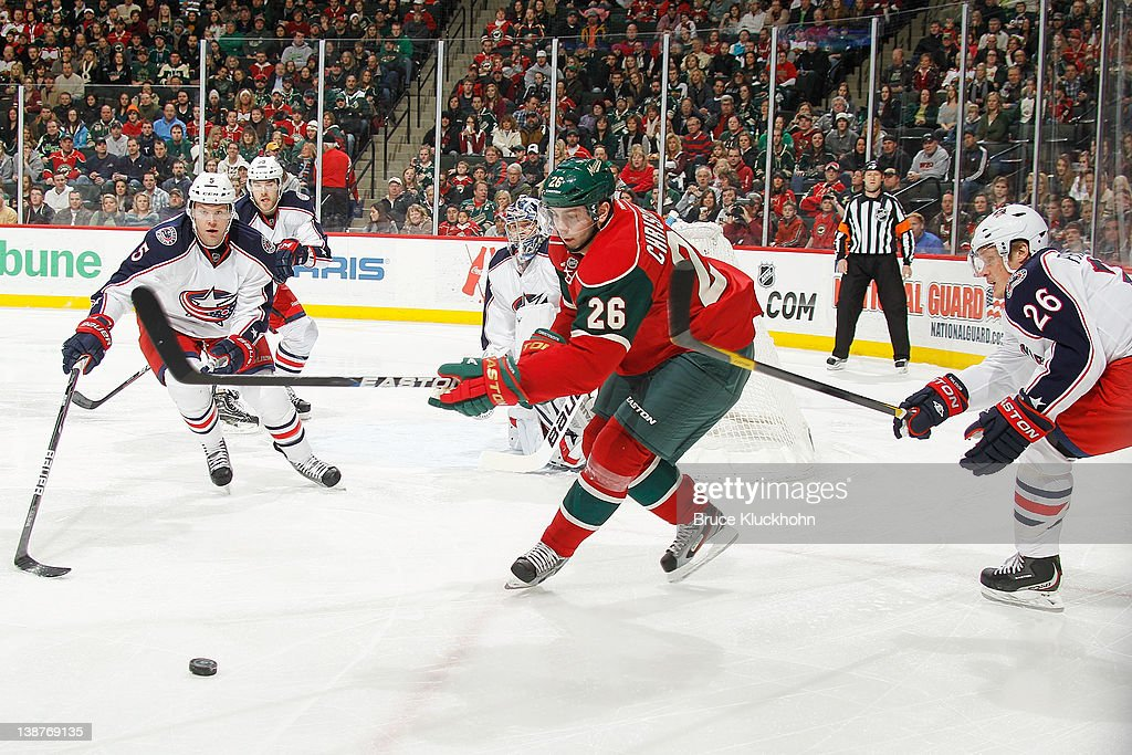 <a gi-track='captionPersonalityLinkClicked' href=/galleries/search?phrase=Erik+Christensen&family=editorial&specificpeople=870252 ng-click='$event.stopPropagation()'>Erik Christensen</a> #26 of the Minnesota Wild skates to the puck with (L-R) Aaron Johnson #5, <a gi-track='captionPersonalityLinkClicked' href=/galleries/search?phrase=Samuel+Pahlsson&family=editorial&specificpeople=206677 ng-click='$event.stopPropagation()'>Samuel Pahlsson</a> #26, and the Columbus Blue Jackets defense closing in during the game at the Xcel Energy Center on February 11, 2012 in St. Paul, Minnesota.