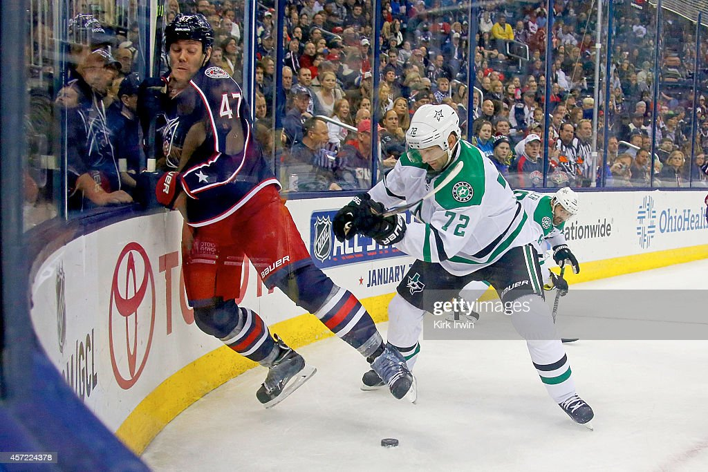 Erik Cole #72 of the Dallas Stars checks Dalton Prout #47 of the Columbus Blue Jackets into the boards while battling for control of the puck during the third period on October 14, 2014 at Nationwide Arena in Columbus, Ohio. Dallas defeated Columbus 4-2.