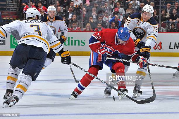 Erik Cole of the Montreal Canadiens is stick checked by Jordan Leopold and Luke Adam of the Buffalo Sabres during the NHL game on November 14 2011 at...