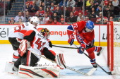 Erik Cole of the Montreal Canadiens slides the puck in the net behind goaltender Craig Anderson the Ottawa Senators during the NHL game on March 23...