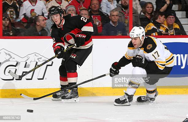 Erik Condra of the Ottawa Senators passes the puck against the outstretched stick of Milan Lucic of the Boston Bruins at Canadian Tire Centre on...