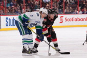 Erik Condra of the Ottawa Senators prepares for a faceoff against David Booth of the Vancouver Canucks during an NHL game at Canadian Tire Centre on...