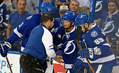 Erik Condra of the Tampa Bay Lightning is helped off the ice by a trainer and Nikita Nesterov against the New York Islanders during the first period...