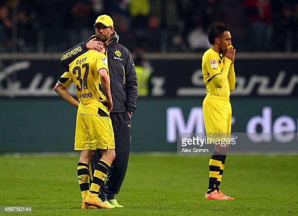 Erik Durm and PierreEmerick Aubameyang of Borussia Dortmund look dejected while head coach Juergen Klopp hugs Durm after the Bundesliga match between...