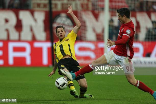 Erik Durm of Borussia Dortmund and Robert Lewandowski of Bayern Munich vie for the ball during the German Cup semi final soccer match between FC...