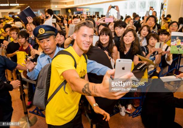 Eric Durm of Borussia Dortmund signs takes a sefie with fans fans after arriving at the airport on July 14 2017 in Tokyo Japan