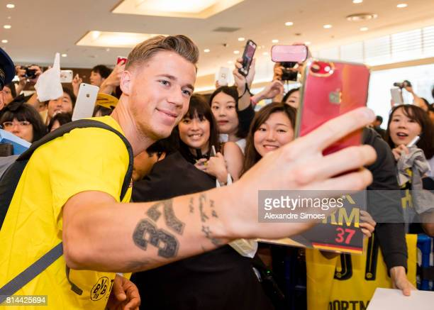 Eric Durm of Borussia Dortmund takes a selfie with fans after arriving at the airport on July 14 2017 in Tokyo Japan