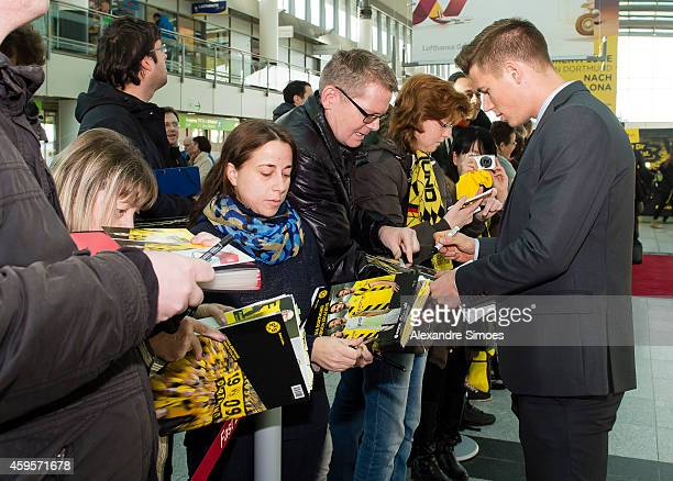 Erik Durm of Borussia Dortmund with the fans at the Dortmund airport prior to their UEFA Champions League match against FC Arsenal at Emirates...