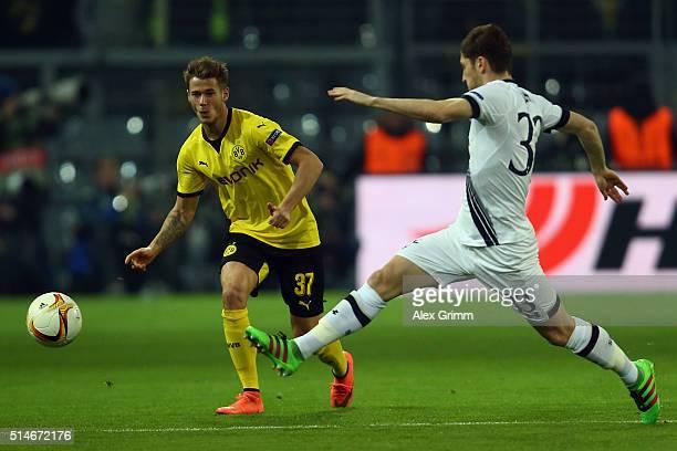 Erik Durm of Dortmund passes the ball past Ben Davies of Tottenham during the UEFA Europa League Round of 16 first leg match between Borussia...
