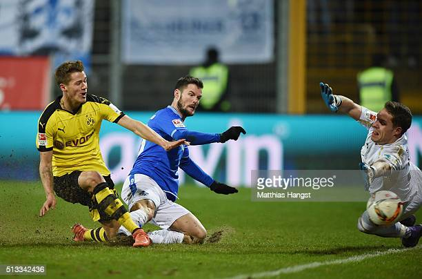 Erik Durm of Dortmund scores his team's second goal past Marcel Heller of Darmstadt and goalkeeper Christian Mathenia of Darmstadt during the...